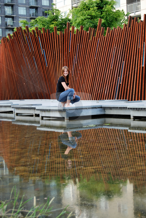 Teen Kneeling Next to Pond - Vertical, Smiling stock photo, Vertically framed outdoor shot of a smiling teenage girl kneeling next to a pond. by Orange Line Media