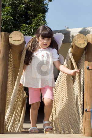 Girl Playing on Rope Bridge stock photo, Vertically framed outdoor shot of a young girl playing on a play set in a park. by Orange Line Media