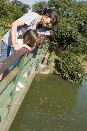 Mother Looking into Pond with Two Daughters stock photo, Vertically framed outdoor shot of a mother standing on bridge looking at fish in pond with her two little daugthers. by Orange Line Media