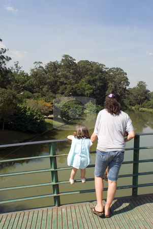 Looking at Pond with Mom stock photo, Outdoor shot of a mother and young daugther standing on bridge looking into a pond. by Orange Line Media