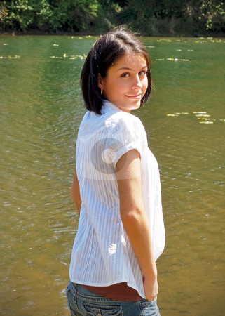 Cute Brunette by the River stock photo, Attractive young woman standing by a river bank and looking back over her shoulder at the camera. Vertically framed shot. by Orange Line Media