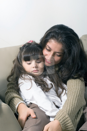 Mother and Daughter stock photo, Mother whispering to her sleepy daughter as she falls asleep in her lap by Orange Line Media