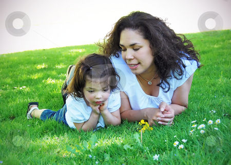Mother and Daughter stock photo, Young, attractive mother and her adorable daughter lying side by side on the grass on a sunny day. Horizontally framed shot. by Orange Line Media