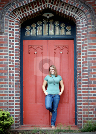 Young Adult Standing in front of Door stock photo, Vertically framed shot of an attractive young adult standing in front of a large door of a brick building. by Orange Line Media