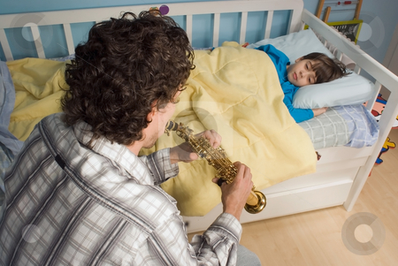 Father and Son stock photo, Father putting his son to sleep by playing him a tune on his saxophone by Orange Line Media