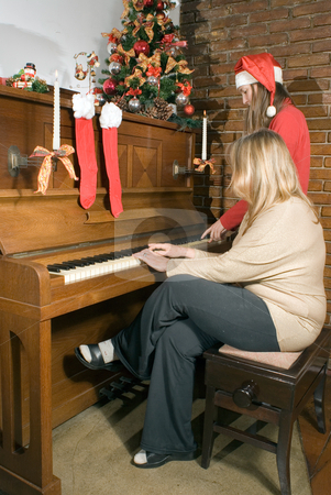 Carols at Christmas stock photo, Mother and daughter sitting at the piano singing Christmas carols. Vertically framed shot. by Orange Line Media