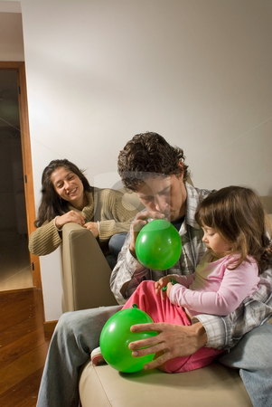 Father and Daughter Blowing Up Balloons stock photo, Father blowing up balloons for his daughter sitting next to him, mother smiling in background. by Orange Line Media