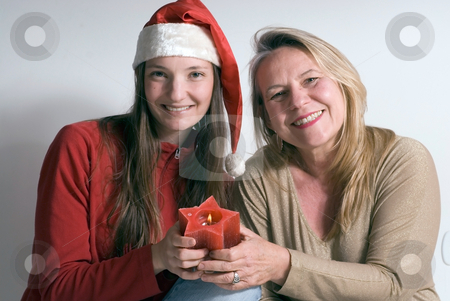 Mother and Daughter stock photo, Mature woman and her daughter getting into the christmas spirit and holding a burning christmas candle. Both women are smiling at the camera by Orange Line Media