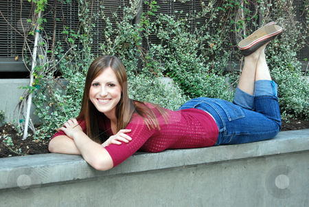 Teen Lying on Plater Edge stock photo, Outdoor shot of a smiling teenage girl lying on the edge of concrete plater. by Orange Line Media