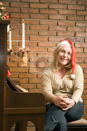 Older Woman Getting in the Christmas Spirit stock photo, Senior woman sitting at an upright piano wearing a santa hat and smiling at the camera. Vertically framed shot. by Orange Line Media