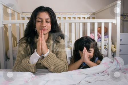 Mother stock photo, Mother and daughter saying their prayers together before going to bed by Orange Line Media