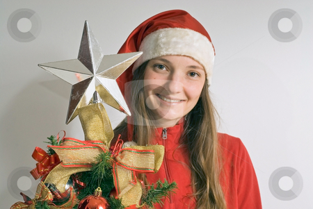 Woman Smiling Next to a Christmas Tree stock photo, A young woman smiling next to a christmas tree. by Orange Line Media