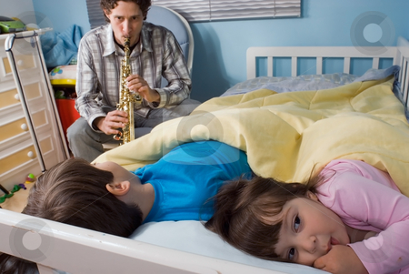 Father and Children stock photo, Young father putting his kids to bed with his music. (In a good way) by Orange Line Media