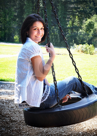 Cute Brunette on a Swing stock photo, Attractive young woman on a tire-swing, smiling at the camera. Vertically framed shot. by Orange Line Media