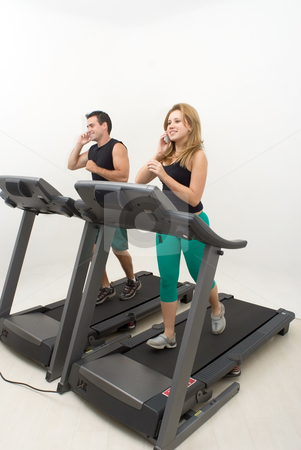 Couple on Treadmill stock photo, Young attractive couple working out on treadmills and talking on their cellphones. Vertically framed shot. by Orange Line Media