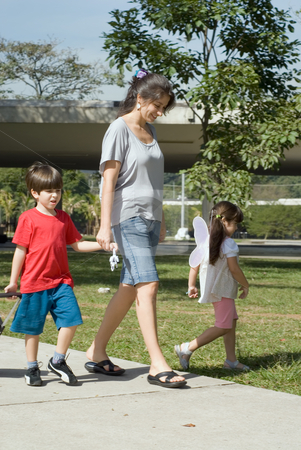 Young Children Walking in Park with Mother stock photo, Vertically framed outdoor shot of a mother walking in a park with her young son and daughter on bright and sunny day. by Orange Line Media