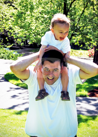 Father and Son stock photo, Little boy squealing with delight as his dad carries him around on his shoulders. by Orange Line Media