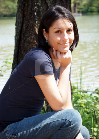 Woman by the River stock photo, Attractive young brunette kneeling by a river bank on a sunny day by Orange Line Media