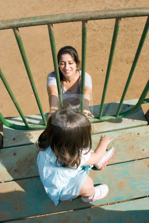Reassuring Mother stock photo, Vertically framed outdoor shot of a smiling mother reassuring her young daughter, as she uses a playground slide. by Orange Line Media