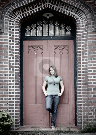 Young Adult Standing in front of Door - Cross Processed stock photo, Vertically framed black and white shot of an attractive young adult standing in front of a large door of a brick building. by Orange Line Media