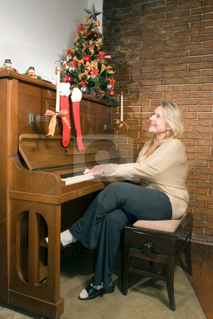 Woman Playing the Piano - Vertical stock photo, Woman playing the piano at Christmas time. Vertically framed shot. by Orange Line Media