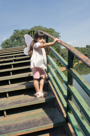 Butterfly Girl on Bridge stock photo, Outdoor shot of a little girl standing on a pedestrian bridge, spanning a pond, wearing butterfly wings. by Orange Line Media