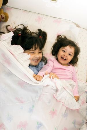 Two Smiling Girls Playing in Bed stock photo, Two smiling little girls playing in bed. by Orange Line Media