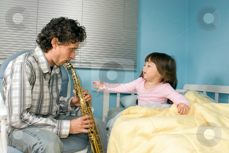 A Father Playing Soprano Saxophone for Daughter Sitting in Bed stock photo, A father playing soprano saxophone for his daughter sitting in bed. by Orange Line Media