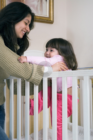 Mother and Daughter stock photo, Mother lifting her daughter out of a crib. Vertically framed shot by Orange Line Media