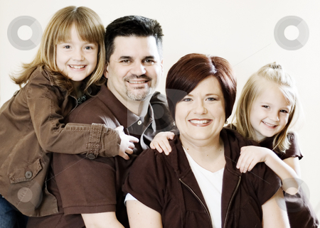 Family Portrait stock photo, Family of four posing together in a studio. Horizontally framed shot against a clean studio background by Orange Line Media