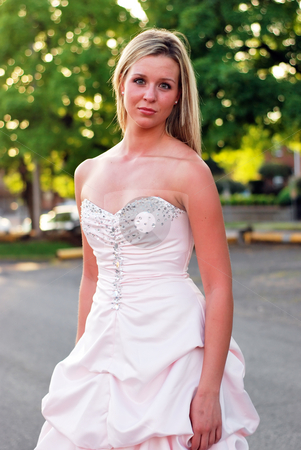 Bridesmaid Standing in Park stock photo, Outdoor shot of an attractive bridesmaid standing in park lined with green trees. by Orange Line Media