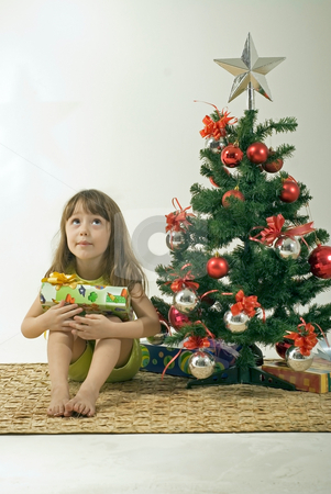 Girl Sitting Next to Christmas Tree Looking Up stock photo, A young girl holding a present looking up towards the ceiling, sitting next to a Christmas tree. by Orange Line Media