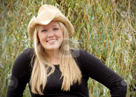 Cute Blond in Cowboy Hat stock photo, Cute blond woman in a cowboy hat sitting outdoors surrounded by tall grass. Horizontally framed shot. by Orange Line Media