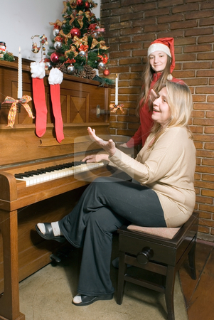 Carols at Christmas 2 stock photo, Mother and daughter sitting at the piano singing Christmas carols. Vertically framed shot. by Orange Line Media