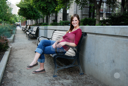 Teen Sitting on Bench - Smiling stock photo, Outdoor shot of a smiling teenage girl sitting on park bench in a beautiful boulevard. by Orange Line Media