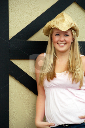Farmers Daughter - Vertical stock photo, Vertically framed outdoor shot of a smiling teenage girl, with blond hair and blue eyes, standing next to barn door wearing a straw cowboy hat. by Orange Line Media