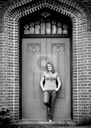 Young Adult Standing in front of Door - Black and White stock photo, Vertically framed black and white shot of an attractive young adult standing in front of a large door of a brick building. by Orange Line Media