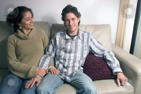 Couple on the Couch stock photo, Attractive young couple sitting together on a couch in their living room by Orange Line Media