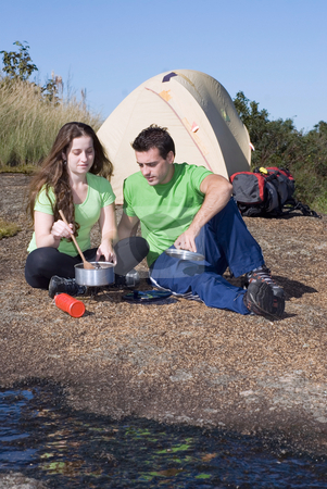Couple Cooking Out - Vertical stock photo, Attractive young couple cooking a meal while on a camping trip. Vertically framed shot by Orange Line Media