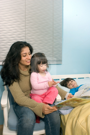 A Mother Reading a Book to Her Children During Bedtime - Vertica stock photo, Vertically framed shot a smiling mother reading a book to a daughter sitting on her lap and son lying in bed. by Orange Line Media