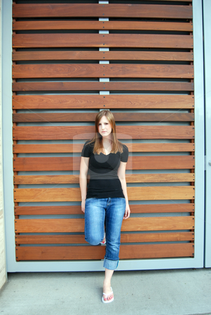 Teen Leaning Against Teak Paneling - Vertical stock photo, Vertically framed outdoor shot of a teenage girl leaning against a Teak paneled wall. by Orange Line Media