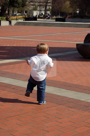 Toddler Walking on Bricks stock photo, Toddler boy walking on a brick pedestrian mall. by Orange Line Media