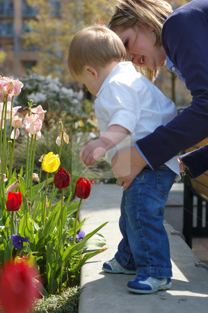 Looking at Flowers - In Close stock photo, Side shot of a mother standing behind her son helping him look at flowers in a planter. by Orange Line Media