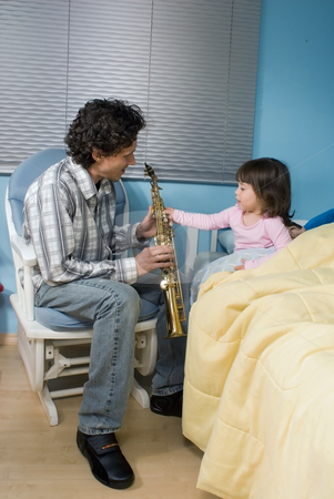 Father and Daughter stock photo, Father and daughter playing the saxophone for his daughter as she gets ready for bed by Orange Line Media