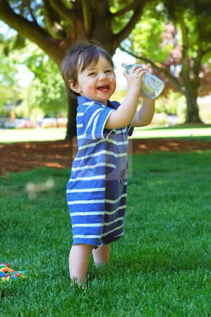 Little Boy stock photo, Cute little boy in blue one-piece suit standing outside holding his bottle and cheering with glee. Vertically framed shot. by Orange Line Media