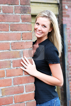 Attractive Blond Woman stock photo, Attractive young blond woman casually dressed smiling at the camera while leaning against the brick wall of an abandoned building. Vertically framed shot. by Orange Line Media