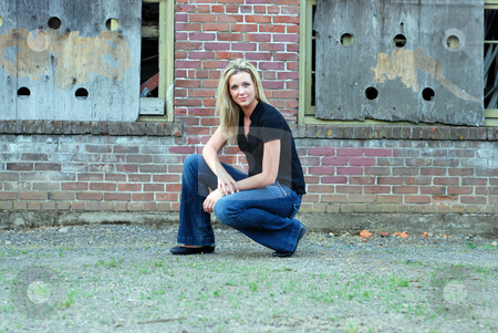 Attractive Blond Woman stock photo, Attractive young blond woman casually dressed smiling at the camera while crouching down in front of the brick wall of an abandoned building. Horizontally framed shot. by Orange Line Media