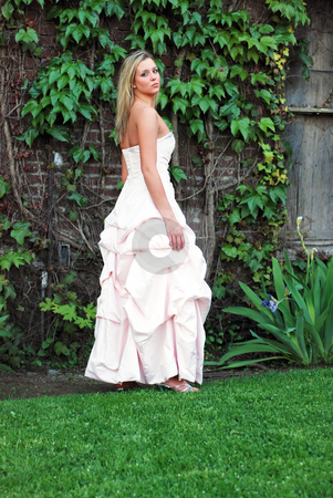 Cute Blond Woman - Vertical stock photo, Attractive blond woman in a bridesmaid's dress standing on a lush green lawn by Orange Line Media