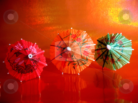 Cocktail Umbrellas stock photo, Close-up shot of three cocktail umbrellas on red glass in front of iridescent red and orange background. by Orange Line Media