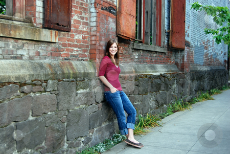 Teen Leaning Against Wall - Horizontal, Smiling stock photo, Horizontally framed outdoor shot of a smiling teenage girl with her hands in her pockets leaning against a brick and stone wall. by Orange Line Media